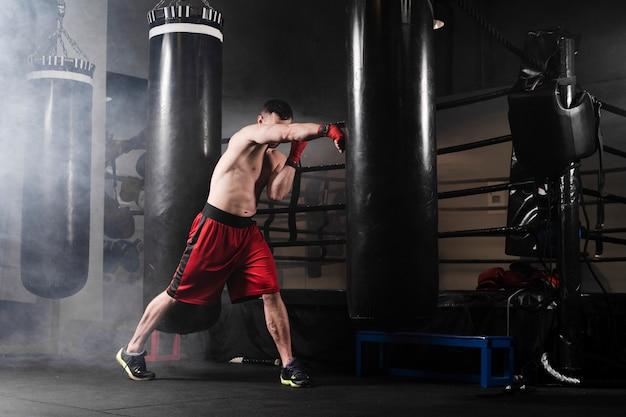 Widok z boku szkolenia człowieka do zawodów bokserskich