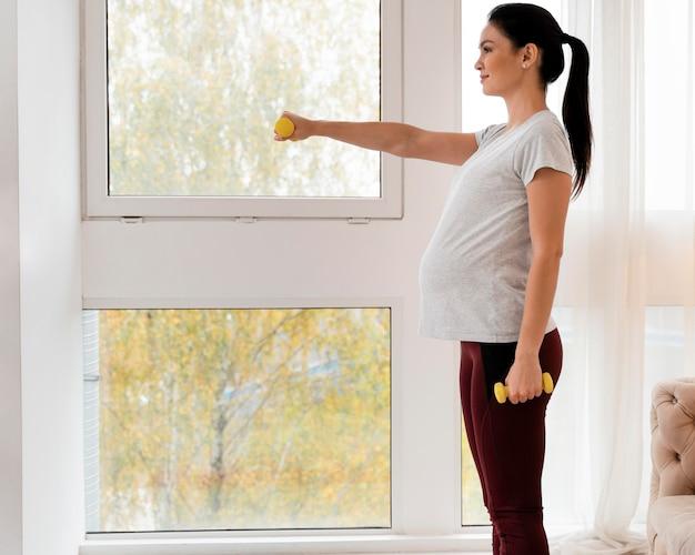 Widok z boku szkolenia kobiety w ciąży z ciężarami z miejsca na kopię
