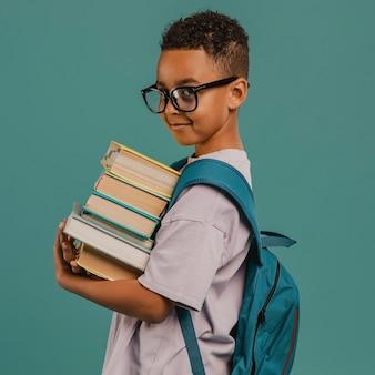 Widok z boku szkoły chłopiec trzyma stos książek