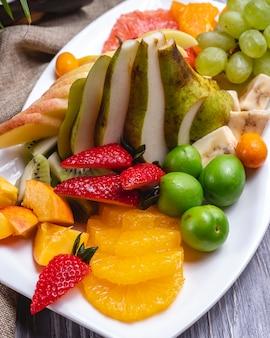 Widok z boku talerz owoców pomarańczowy truskawkowy bananowy kiwi gruszka winogrona i wiśnia śliwka