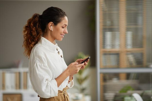 Widok z boku talii na uśmiechniętą elegancką bizneswoman za pomocą bezprzewodowych słuchawek i trzymając smartfon stojąc w domu lub w biurze, kopiuj przestrzeń