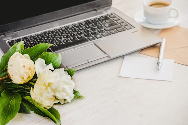 Widok z boku talii z komputerem, bukiet kwiatów piwonii, filiżanka kawy, pusta karta i koperta kraft.