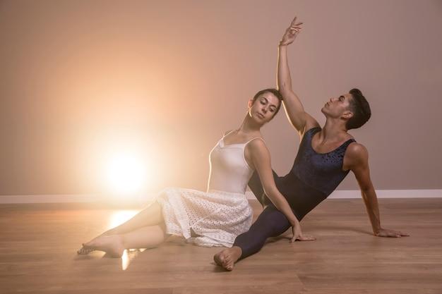 Widok z boku tancerzy baletowych siedzi pozować