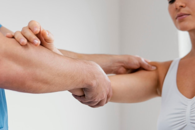 Widok z boku terapeuty osteopatycznego mężczyzny sprawdzającego staw barkowy pacjentki
