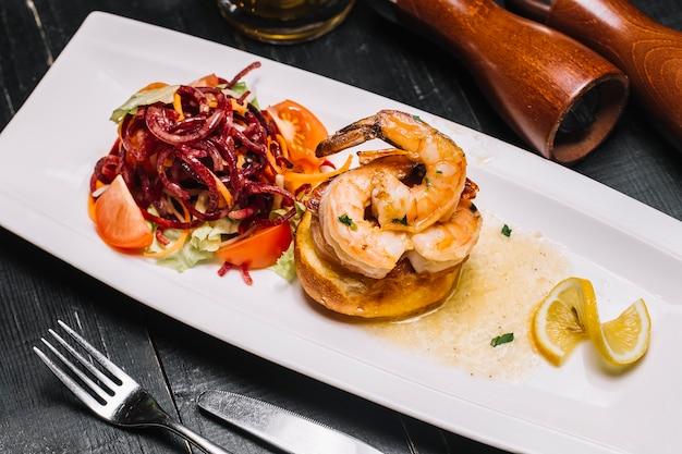 Widok z boku tosty krewetkowe z sałatką warzywną i plasterkiem cytryny