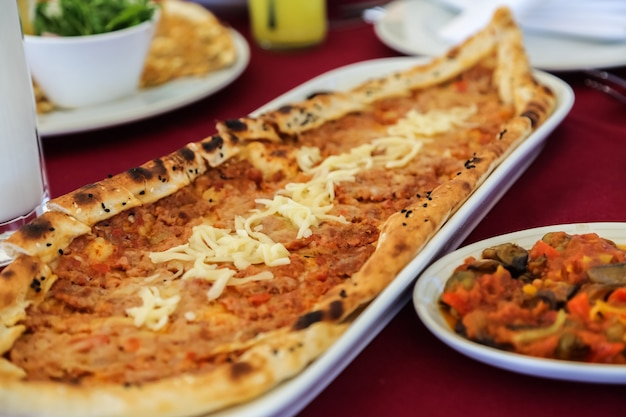 Widok z boku tradycyjne tureckie danie pide mięsne z serem