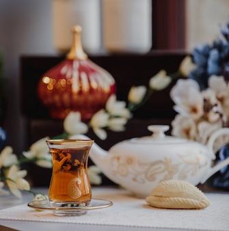 Widok z boku tradycyjnego tureckiego azerskiego szkła w kształcie gruszki do armudu z czarnej herbaty z shekerbura na stole