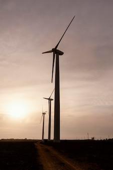 Widok z boku turbin wiatrowych o zachodzie słońca wytwarzających energię