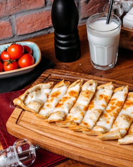 Widok z boku tureckiej pide z serem ułożone na drewnianej desce do krojenia