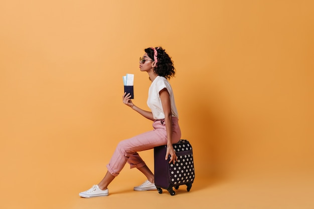 Widok z boku turysty kobieta siedząca na walizce