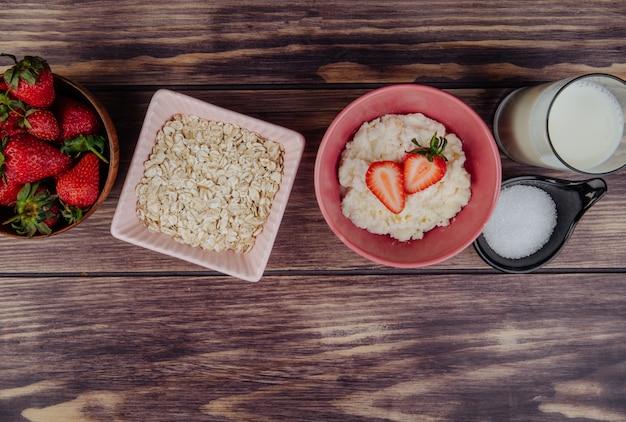Widok z boku twarożku ze świeżymi truskawkami w misce płatki owsiane, cukier i szklanka mleka na rustykalnym drewnie