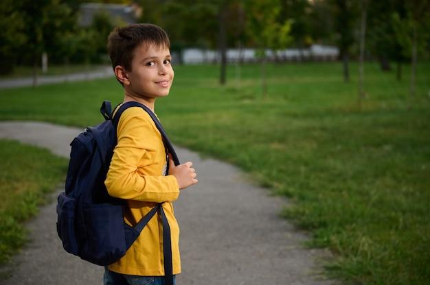 Widok z boku ucznia z plecakiem na tornister idący ścieżką w publicznym parku, idący do domu po szkole, ładny uśmiechający się do kamery