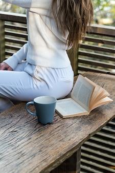 Widok z boku upraw nie do poznania kobieta siedzi na drewnianej ławce na tarasie z książką i kubkiem ciepłego napoju o zachodzie słońca