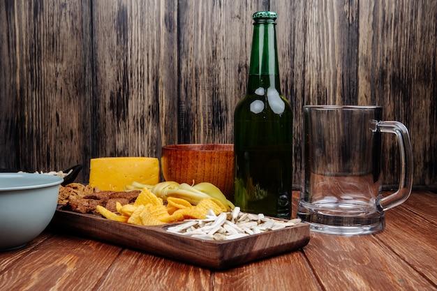 Widok z boku urozmaiconego słonego piwa na drewnianym talerzu z butelką piwa na rustykalnym drewnie