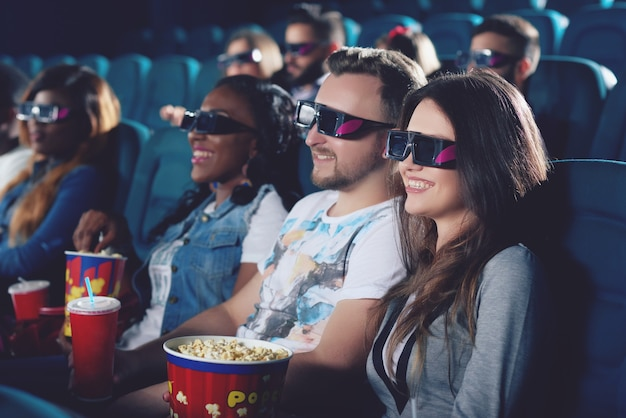 Widok z boku uśmiechnięta brunetka trzyma popcorn i patrząc na projektor. grupa przyjaciół oglądając film w nowoczesnej sali kinowej i uśmiechając się razem.