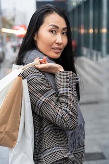 Widok z boku uśmiechnięta kobieta trzyma torby