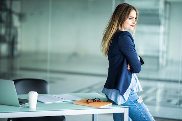 Widok z boku uśmiechnięta młoda bizneswoman stoi w swoim miejscu pracy
