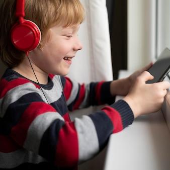 Widok z boku uśmiechniętego chłopca za pomocą tabletu ze słuchawkami