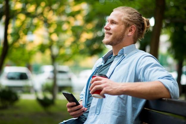 Widok z boku uśmiechniętego człowieka na zewnątrz ze smartfonem
