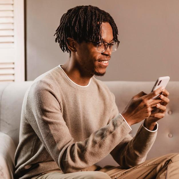 Widok z boku uśmiechniętego człowieka w domu przy użyciu smartfona