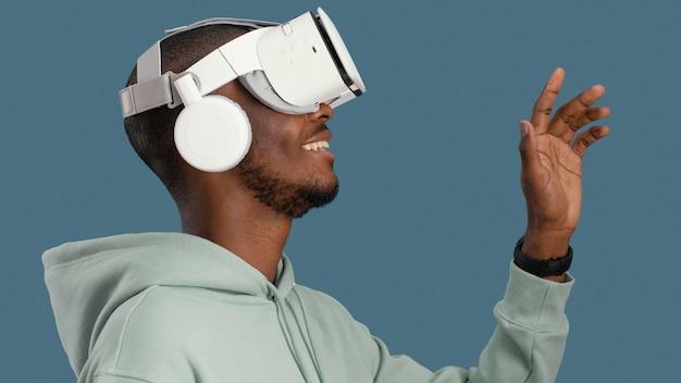 Widok z boku uśmiechniętego człowieka z zestawem słuchawkowym wirtualnej rzeczywistości