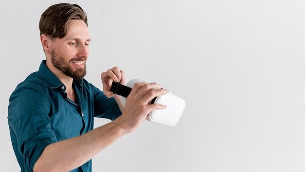 Widok z boku uśmiechniętego mężczyzny trzymającego zestaw słuchawkowy wirtualnej rzeczywistości z miejsca na kopię