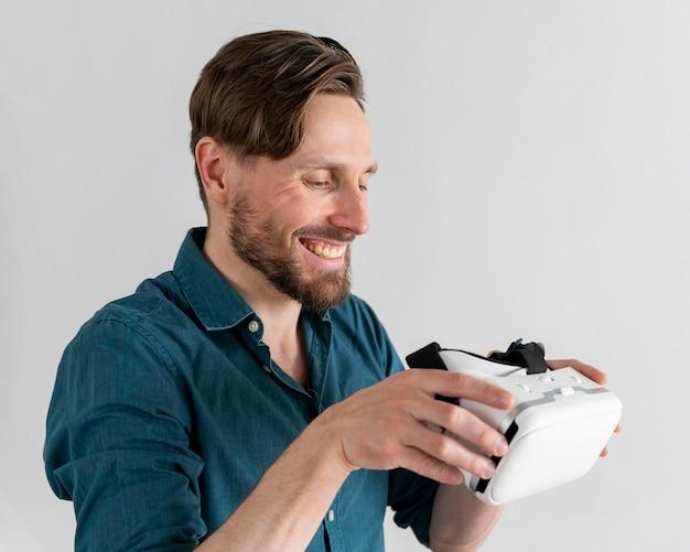 Widok z boku uśmiechniętego mężczyzny trzymającego zestaw słuchawkowy wirtualnej rzeczywistości