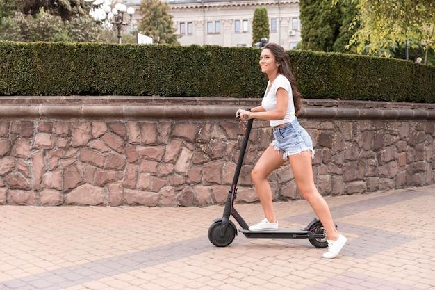 Widok z boku uśmiechniętej kobiety jeżdżącej skuterem w mieście