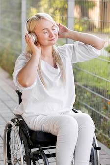 Widok z boku uśmiechniętej kobiety na wózku inwalidzkim ze słuchawkami