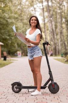 Widok z boku uśmiechniętej kobiety patrząc na mapę obok skutera elektrycznego