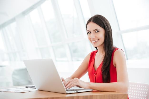 Widok z boku uśmiechniętej kobiety siedzącej przy stole z laptopem w biurze i patrzącej na kamerę