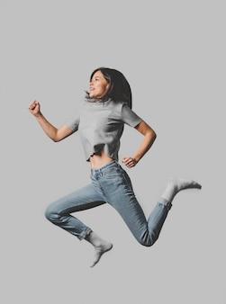 Widok z boku uśmiechniętej kobiety skaczącej w powietrzu