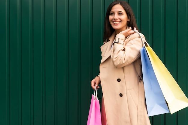 Widok z boku uśmiechniętej kobiety trzymającej torby na zakupy z miejsca na kopię