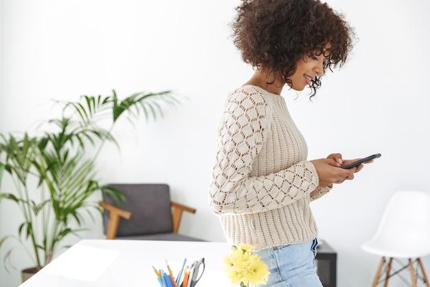 Widok z boku uśmiechniętej kobiety ubranej w zwykłe ubrania przy użyciu smartfona stojącej przy stole w biurze
