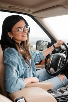 Widok z boku uśmiechniętej kobiety w okularach, podróżującej samotnie samochodem