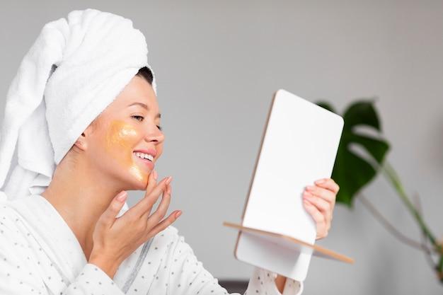 Widok z boku uśmiechniętej kobiety w szlafroku, stosując produkty do pielęgnacji skóry