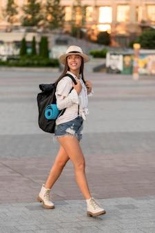 Widok z boku uśmiechniętej kobiety z kapeluszem niosącym plecak podczas samotnej podróży