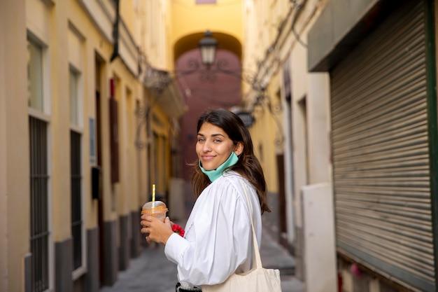 Widok z boku uśmiechniętej kobiety z torby na zakupy