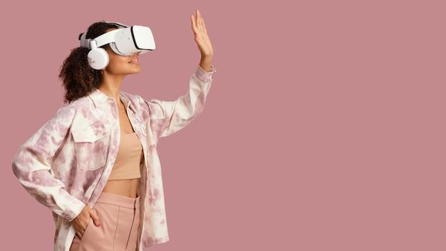 Widok z boku uśmiechniętej kobiety z zestawem słuchawkowym wirtualnej rzeczywistości i miejsca na kopię