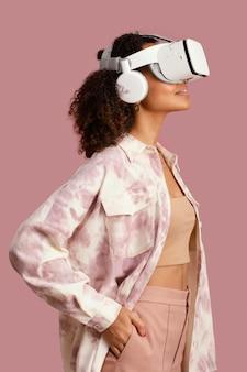 Widok z boku uśmiechniętej kobiety z zestawem słuchawkowym wirtualnej rzeczywistości