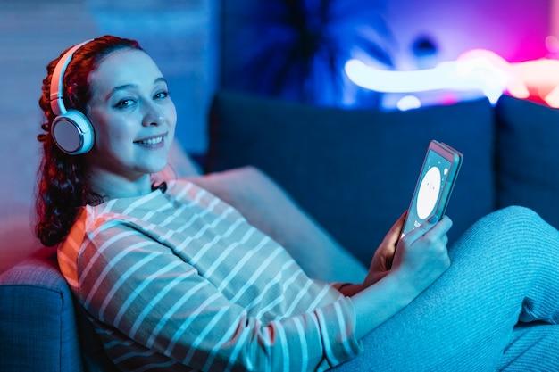 Widok z boku uśmiechniętej kobiety za pomocą tabletu i słuchawek w domu