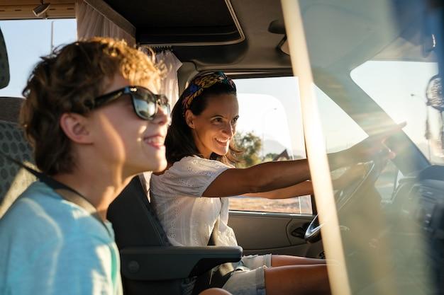 Widok z boku uśmiechniętej matki siedzącej na siedzeniu kierowcy samochodu kempingowego i wskazującej drogę podczas podróży z synem podczas letnich wakacji