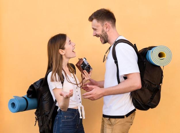 Widok z boku uśmiechniętej pary turystycznej z plecakami i aparatem