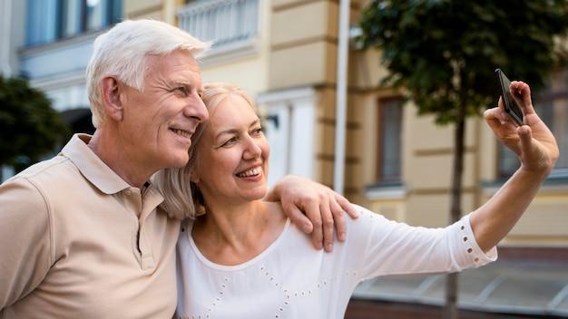 Widok z boku uśmiechniętej starszej pary na zewnątrz, biorąc selfie