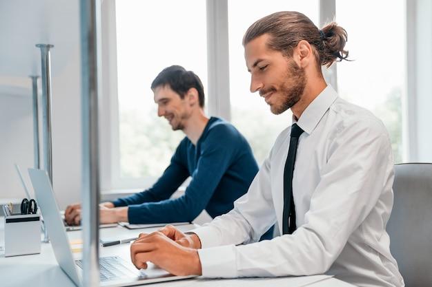 Widok z boku uśmiechnięty biznesmen pracujący na laptopie