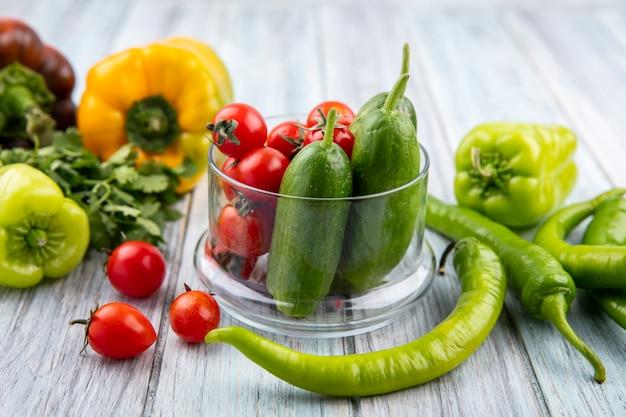 Widok z boku warzyw jak pomidor i ogórek w szklanej misce z kolendrą na drewnie