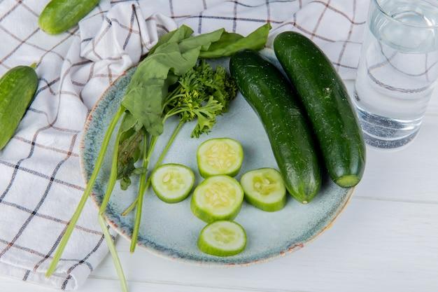 Widok z boku warzyw w całości i pokrojonej w plasterki ogórkowej szpinakowej kolendry z ogórkami na tkaninie i wody detoksykacyjnej na drewnianym stole