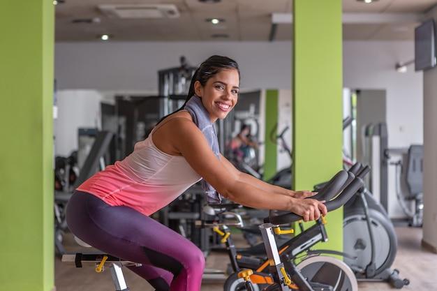 Widok z boku wesoła młoda dorosła kobieta patrząc na kamery w activewear robi cardio na rowerze stacjonarnym w siłowni.