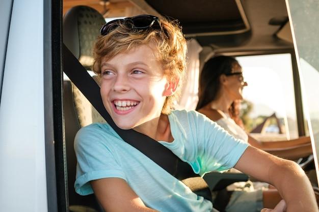 Widok z boku wesołego preteen chłopca patrzącego przez otwarte okno podczas podróży z matką prowadzącą samochód w letni dzień