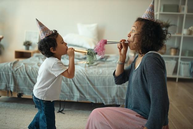 Widok z boku wesołej młodej samicy rasy mieszanej i jej uroczego małego synka w stożkowych czapkach, dmuchających w gwizdek podczas świętowania urodzin samotnie w domu podczas kwarantanny